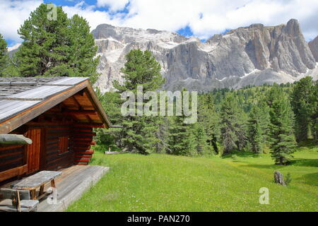 Sella group mountains viewed from a hiking path near Sella pass with a mountain hut in the foreground, Selva, Val Gardena, Dolomites, Italy - Stock Photo