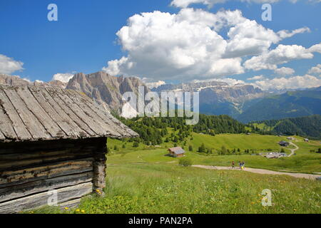 Puez Odle mountain and Sella Group mountains viewed from a hiking path near Raiser Pass with mountain hut in foreground, Val Gardena, Dolomites, Italy - Stock Photo
