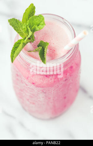 Fruit pink smoothie in a glass jar on a white marble. Minimalist style. Trend vintage toned. - Stock Photo