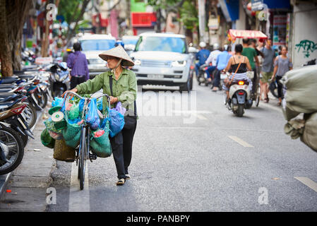 A woman carrying her bicycle in Hanoi, Vietnam, wearing a traditional conical hat. Women selling products on their bicycles are a common site in Hanoi - Stock Photo