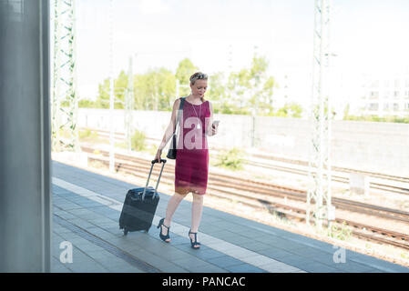 Mature businesswoman with smartphone and suitcase walking at platform - Stock Photo