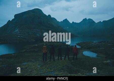 Norway, Lofoten, Moskensoy, Five young man looking at Agvatnet lake at dawn - Stock Photo