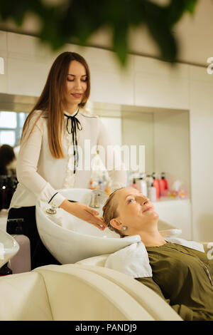 Positive happy hairdresser working with her client - Stock Photo