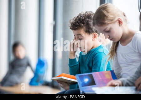 Tired schoolboy with book in school - Stock Photo