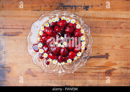 Homemade strawberry cake with red grape juice glaze and daisy flower decoration on glass cake stand - Stock Photo