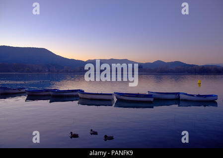 Tranquil peaceful lake scene photo with boats and ducks at sunset - Stock Photo