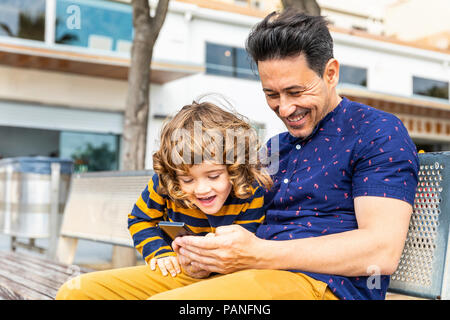 Spain, Barcelona, happy father and son with a smartphone sitting on bench - Stock Photo