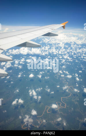 Airplane wing and sinewy river winding through farmland, high above Indonesia - Stock Photo