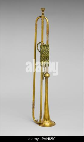 Natural Trumpet. Culture: German. Dimensions: Depth (Without crook or mouthpiece): 25 11/16 in. (65.3 cm)  Diameter (Of bell): 4 7/16 in. (11.3 cm). Maker: Johann Wilhelm Haas (German, Nuremberg 1649-1723 Nuremberg). Date: late 17th century.  Natural trumpets such as this were used in the military and in royal pagentry. The production and playing of trumpets in Germany during the seventeenth and early eighteenth centuries was strictly regulated by a guild system. The four generations of the Haas family were the most prolific and prominent dynasty of brass instrument makers working in Nuremberg - Stock Photo