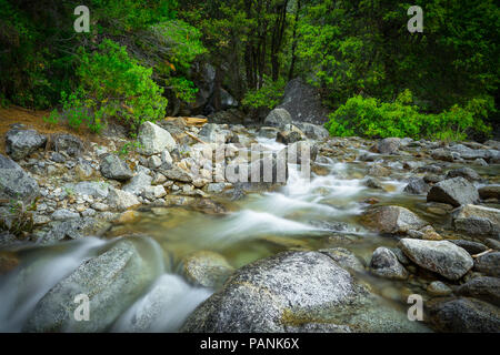Babbling Brook with soft flowing water and rocky landscape - base of Tamarack Creek, Yosemite National Park - Stock Photo