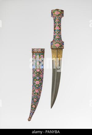 Dagger with Sheath. Culture: Iranian. Dimensions: L. 17 1/16 in. (43.3 cm); Wt. 23.4 oz. (664.0 g); Dagger: L. 15 1/8 in. (38.4 cm); L. of blade 9 1/8 in. (23.2 cm); W. 2 in. (5.1 cm); Wt. 15 oz. (413.0 g); Scabbard: L. 11 in. (28.1 cm); Wt. 9 oz. (251.0 g). Date: late 18th-early 19th century.  Brilliant colors and lush floral patterns are typical of Qajar painted enamels. While here opaque pink, blue, and white predominate, the background color is a deep translucent green applied to a shimmering gold ground. The artist has signed his work on the back of the scabbard, Mahmud. Museum: Metropoli - Stock Photo