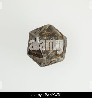Twenty-sided die (icosahedron) with faces inscribed with Greek letters. Dimensions: Height: 3.2 x L: 3.8 x W: 3.4 cm (1 1/4 x 1 1/2 x 1 5/16 in.). Date: 2nd century B.C.-4th century A.D..  A number of polyhedral dice made in various materials have survived from the Hellenistic and Roman periods, usually from ancient Egypt when known. Several are in the Egyptian or Greek and Roman collections at the Museum. The icosahedron - 20-sided polyhedron - is frequent. Most often each face of the die is inscribed with a number in Greek and/or Latin up to the number of faces on the polyhedron.   Nothing s - Stock Photo