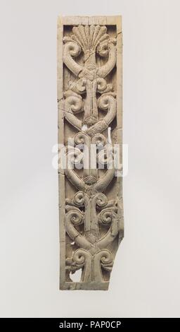 Furniture plaque carved in relief with volutes and a palmette. Culture: Assyrian. Dimensions: 9.84 x 2.32 x 0.39 in. (24.99 x 5.89 x 0.99 cm). Date: ca. 8th century B.C..  This ivory panel was found in a storage room in Fort Shalmaneser, a royal building at Nimrud that was used to store booty and tribute collected by the Assyrians while on military campaign. Like many other panels from the same storage room, it was part of a chair or couch back or the headboard of a bed. Twenty pieces of furniture were discovered stacked in orderly rows in this room, where they had been stored before the destr - Stock Photo