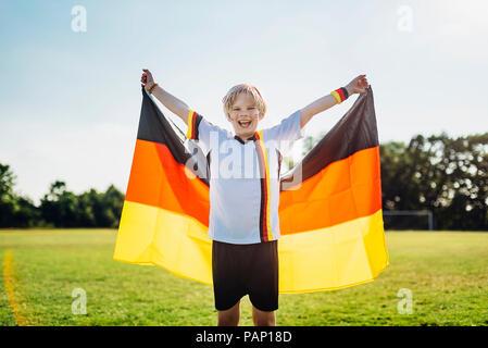 Boy, enthusiastic for soccer world championship, waving German flag