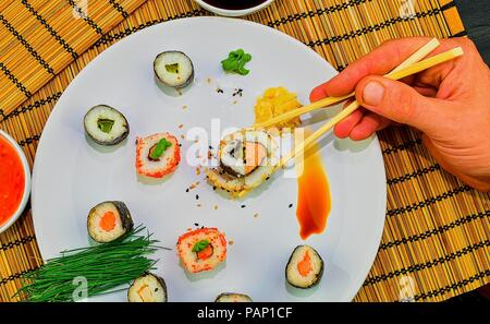 Eating roll sushi in japanese restaurant, hand with chopsticks close -up. A man's hand holding sushi with chopsticks. - Stock Photo