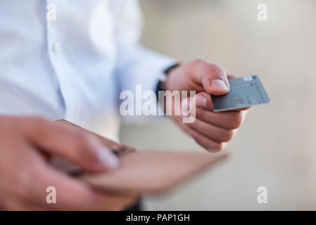Close-up of businessman holding credit card - Stock Photo