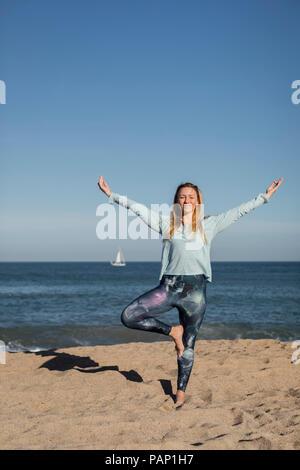 Woman doing yoga on the beach, tree position - Stock Photo