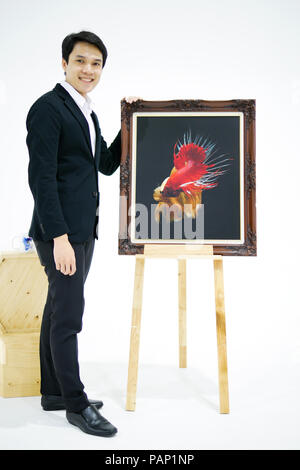 Smart Asian men is presenting the beautiful siamese fighting fish (betta) photo in the museum exhibition. - Stock Photo