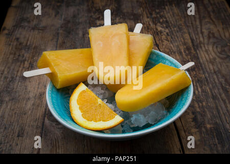 Home-made orange popsicles in bowl - Stock Photo
