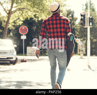 Cool young man with skateboard walking in the city, - Stock Photo