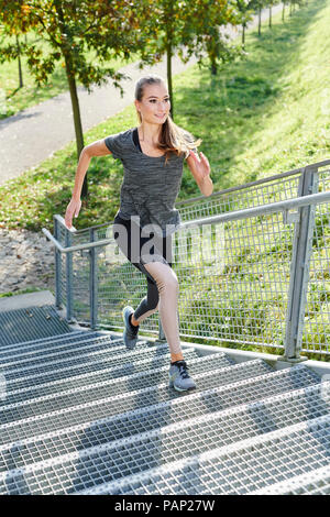 Young woman running on stairs in a park - Stock Photo