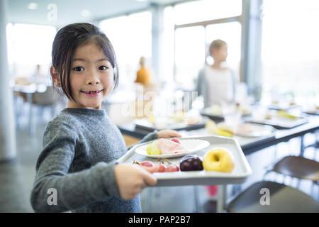 Portrait of smiling schoolgirl carrying tray in school canteen - Stock Photo
