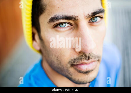 Portrait of young man with blue eyes and stubble - Stock Photo