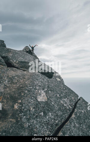 Norway, Lofoten, Moskenesoy, Young man waving from Hermannsdalstinden - Stock Photo