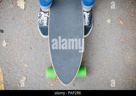 Close-up of feet next to skateboard