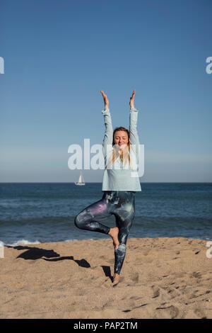 Woman doing yoga on the beach - Stock Photo