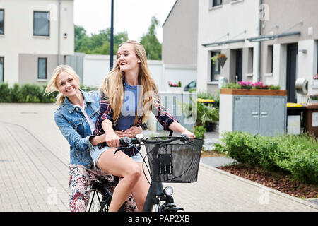 Two happy young women riding bicycle together on one bike - Stock Photo