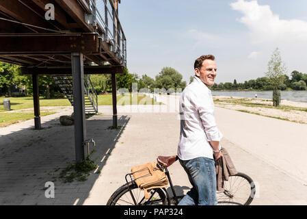 Mature man with bike at Rhine riverbank - Stock Photo