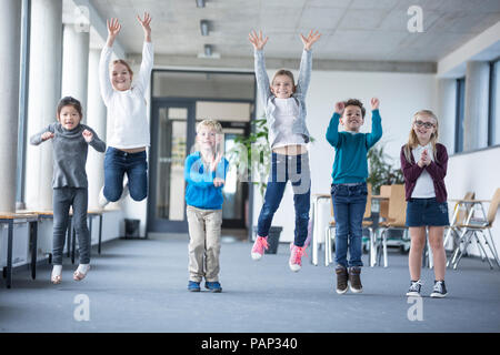 Excited pupils jumping on school corridor - Stock Photo