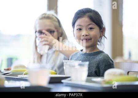 Portrait of smiling schoolgirl with classmate in school canteen - Stock Photo