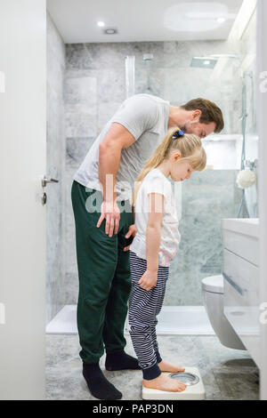 Father and daughter checking weight on bathroom scales - Stock Photo