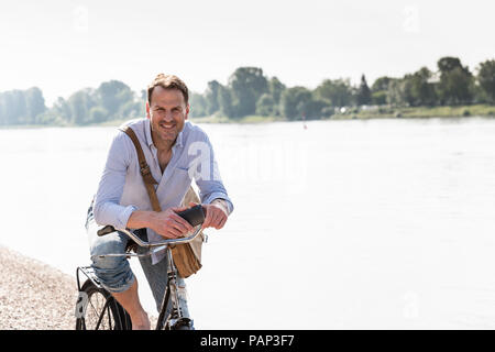 Mature man with bike and smartphone at Rhine riverbank - Stock Photo