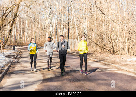 Friends running on a road in a park - Stock Photo