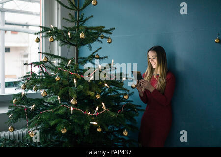 Smiling woman standing besides decorated Christmas tree using tablet - Stock Photo