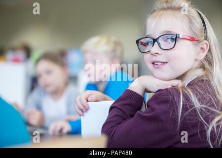 Portrait of smiling schoolgirl with classmates in class - Stock Photo