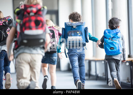 Rear view of pupils rushing down school corridor - Stock Photo