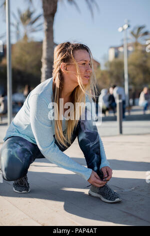 Spain, Barcelona, woman tying running shoe on beach promenade - Stock Photo