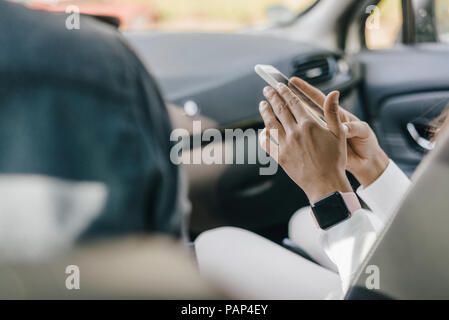 Young businesswoman sitting in car, using smartphone - Stock Photo