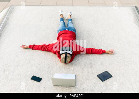 Senior woman lying on the ground wearing VR glasses next to mobile devices - Stock Photo
