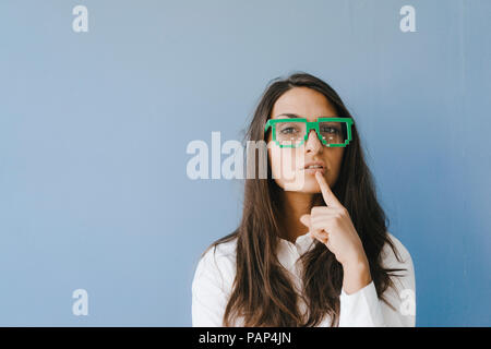 Young woman wearing pixel glasses, putting finger on mouth - Stock Photo