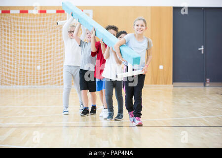 Pupils carrying balance beam in gym class - Stock Photo