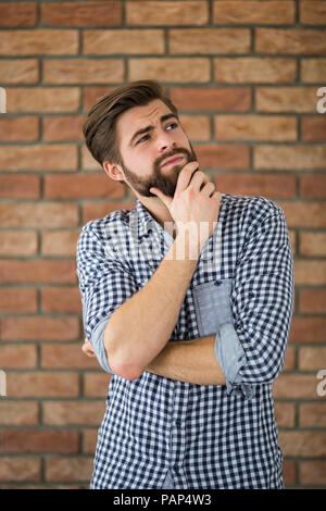 Portrait of bearded young man in front of brick wall thinking - Stock Photo