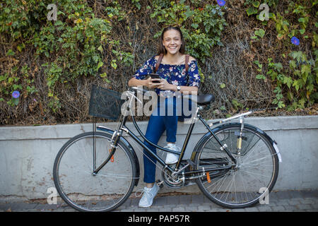 Portrait of smiling teenage girl with cell phone and bicycle - Stock Photo