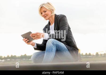 Smiling senior businesswoman sitting with tablet outdoors - Stock Photo