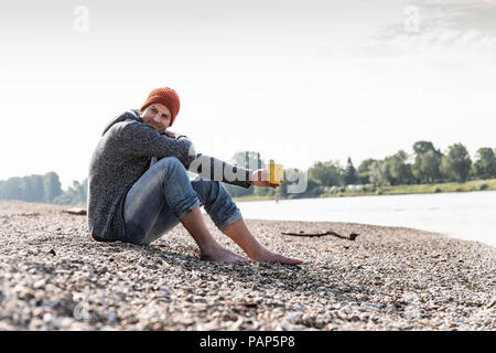 Mature man wearing red beanie and drinking coffee at Rhine riverbank - Stock Photo