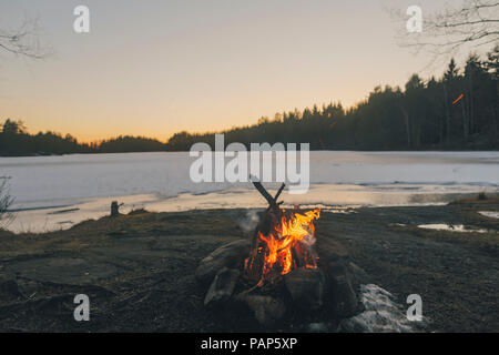 Sweden, Sodermanland, campfire at lakeside in winter - Stock Photo